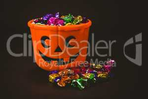 Bucket with colorful wrapped chocolates during Halloween