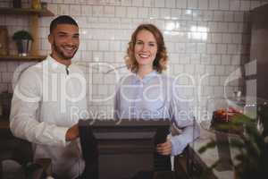 Portrait of smiling waitress and male owner standing by computer