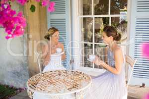 Bride and bridesmaid having coffee in yard