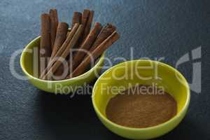 Cinnamon sticks and powder in a bowl