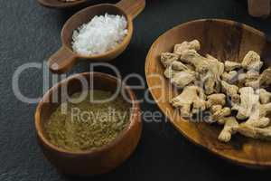 Dried ginger and coriander powder on black background