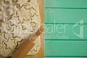 Overhead view of star shape cookies on dough and rolling on cutting board
