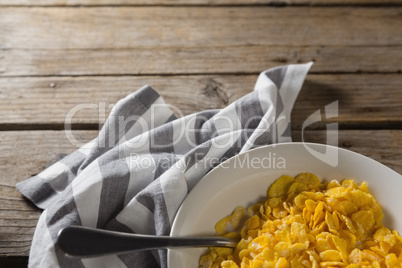Bowl of wheaties cereal and spoon with napkin