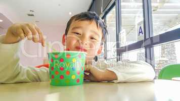 Cute Young Chinese and Caucasian Boy Enjoying Eating His Frozen
