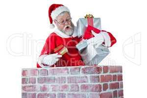 Santa claus placing gift box into a chimney