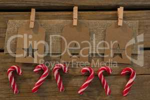High angle view of star shape decoration with burlap and clothespin by candy canes