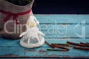 Sack, cinnamon stick and christmas decoration of wooden plank