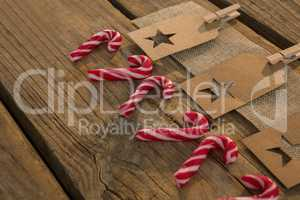 High angle view of star shape decoration with burlap and clothespin by candy canes on table