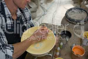 Male potters painting a bowl in pottery workshop