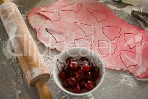 Red cherries in bowl with cookies dough and rolling pin