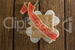 Wrapped gift, ribbon and scissors on wooden plank