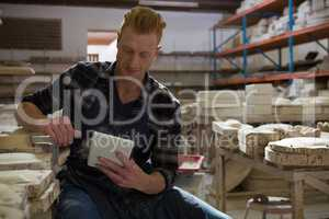 Male potter using digital tablet in pottery workshop