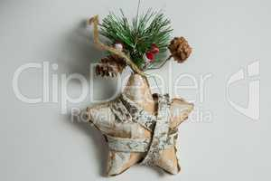 Close up of star shape decoration with pine cone and twig