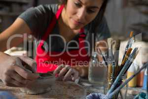 Female potter molding a bowl with hand tool