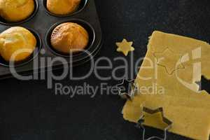Plain cupcakes in baking tray with star shape dough and cutter