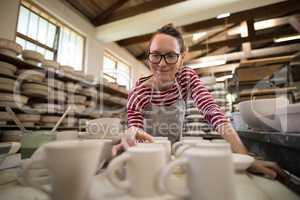 Woman checking mugs at worktop