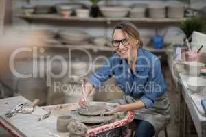 Portrait of female potter molding plate with hand tool