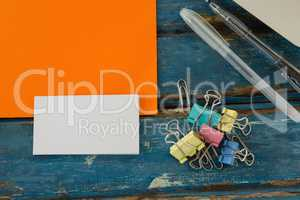 Book, paper clip, visiting cards and blank paper on wooden plank