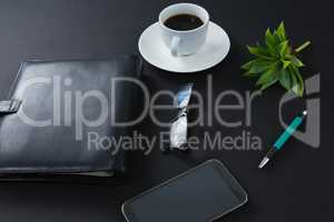 Black coffee, flora, pen, spectacles, mobile phone and organizer on black background