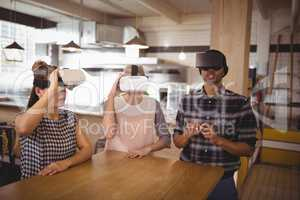 Young friends sitting with virtual reality headsets at coffee shop
