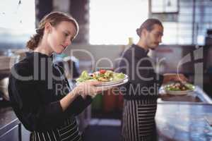 Young wait staff holding fresh salad plates while standing in commercial kitchen