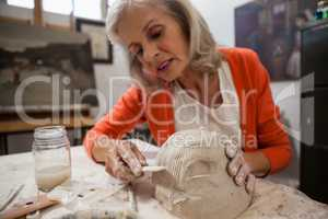 Attentive senior woman shaping a molded clay