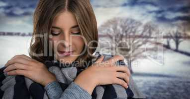 Woman wearing scarf keeping warm in snow landscape with bare tree