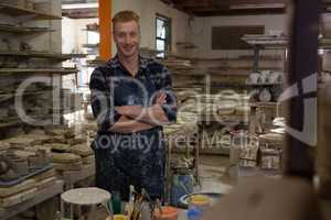 Male potter standing with arms crossed in pottery workshop