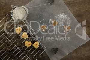 Sieve with icing sugar cookies on cooling rack