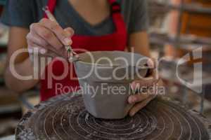Female potter molding a mug with hand tool