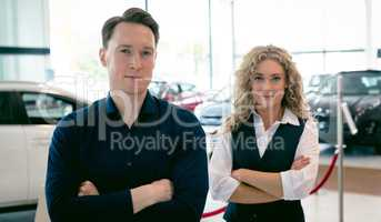 Portrait of entrepreneurs standing in car showroom