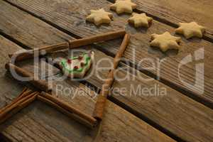 Close up of star shape cookies by Christmas tree made with cinnamon stick