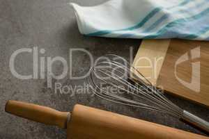 Rolling pin, whisker, chopping board and cloth on table