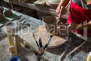 Female potter carving mug