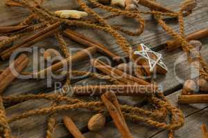 Close up of rope with star shape cookies and cinnamon sticks by walnuts