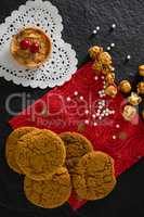 Tart and cookies with pearls on red place mat