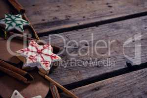 Cinnamon sticks, cookies and christmas decoration on wooden plank