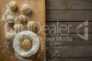 Dough ball placed over flour on a wooden table