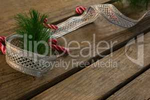 High angle view of candy canes with ribbon and pine needles on table