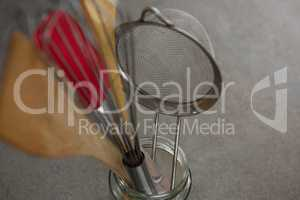 Whisker, wooden spoon, strainer and spatula on glass jar