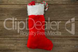 Wrapped gift box and candy cane in stocking against wooden wall