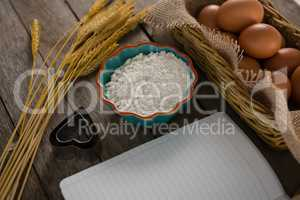 Book, eggs, flour, cookie cutter and wheat stem kept on a table