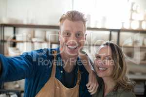 Happy male and female potter standing together in pottery workshop