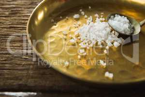 Salt in spoon and plate on wooden table
