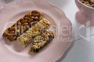 Granola bar in plate on white background