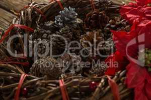 Close up of artificial nest with pine cones and poinsettia flowers
