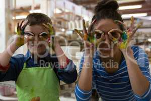 Mother and son gesturing in pottery workshop
