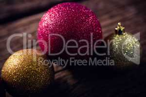 Christmas baubles on wooden plank