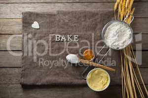Wheat stem, wear flour, sieve, spoon placed over a cloth on wooden table