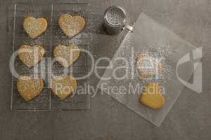 Raw heart shape cookies on baking tray with flour shaker strainer and wax paper